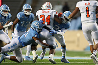 CHAPEL HILL, NC - NOVEMBER 23: Chazz Surratt #21  of the University of North Carolina Dominique Ross #3 of the University of North Carolina stop Tyray Devezin #34 on fourth down during a game between Mercer University and University of North Carolina at Kenan Memorial Stadium on November 23, 2019 in Chapel Hill, North Carolina.