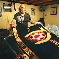 Jimmy shows off some of the flags he maintains for the Ulster Defence Association (UDA), a loyalist paramilitary group. He has been with the organisation from the early vigilante days through the 'Troubles' (a period of intercommunal violence and strife which lasted for approximately 3 decades from the 1960s to 1998, when the Good Friday Agreement ended outright hostilities). His son was murdered by the republican Irish National Liberation Army (INLA).
