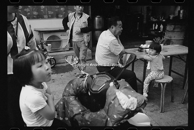 Shou County, Anhui province, China - A family enjoys breakfast at a food stall, May 2017. Shou County, formerly known as Shouchun and Shouyang, was the site of the fourth capital of the former State of Chu from 241 BC.