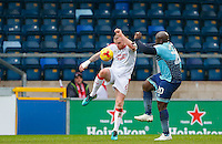 Mark Connolly of Crawley Town clears from Adebayo Akinfenwa of Wycombe Wanderers during the Sky Bet League 2 match between Wycombe Wanderers and Crawley Town at Adams Park, High Wycombe, England on 25 February 2017. Photo by Andy Rowland / PRiME Media Images.