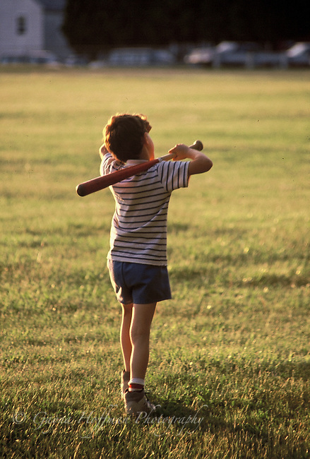 Young boy walking away with bat on shoulder.