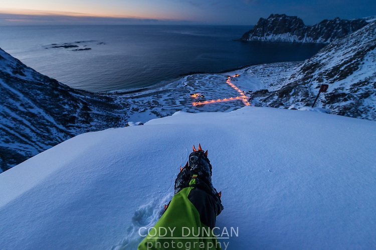 Feet with crampons on mountain peak overlooking Haukland beach in winter, Vestvågøy, Lofoten Islands, Norway