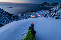 Feet with crampons on mountain peak overlooking Haukland beach in winter, Vestvågøy, Lofoten Islands, Norway