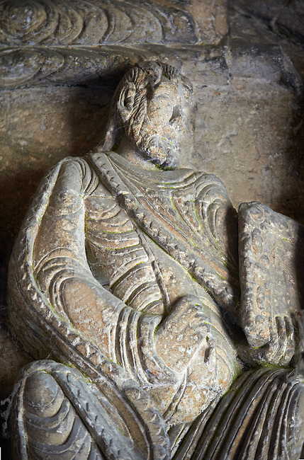 "Early Anglo Saxon sulptures of an Apostle holding a book now part of the south porch of Malmesbury Abbey, Wiltshire, England. The apostles, apart from Peter who holds a crude key, have no distinguishing feature to allow identification. Some are holding books, none have halos and some hold their heads at awkward angles. These three styles are typical of Anglo Saxon art. The two panels are 10 ft long and 4ft 6"" high are date from the original Ango Saxon church of 705. They were probablbly built into the proch during the Norman rebuilding. The style of these sculptures is of the Roman Byzantine style and were probably sculpted by masions from Gaul.  Malmesbury Abbey, Wiltshire, England"