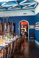 The blue dining room laid for breakfast at the Augill Castle with a view through to the sitting room.