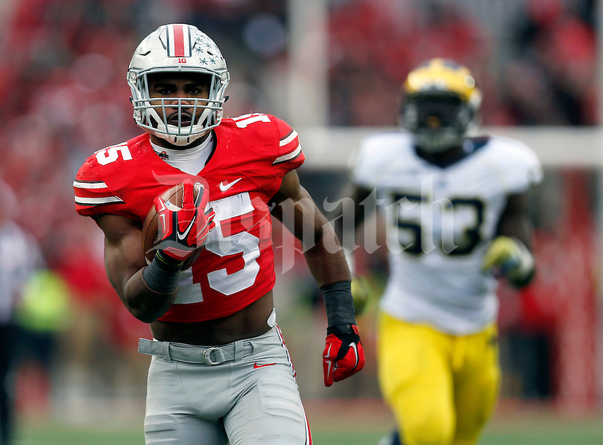 Ohio State Buckeyes running back Ezekiel Elliott (15) runs for a touchdown past Michigan Wolverines defensive end Mario Ojemudia (53) during the fourth quarter of the NCAA football game against Michigan at Ohio Stadium on Saturday, November 29, 2014. (Columbus Dispatch photo by Jonathan Quilter)