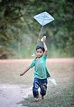 Nhouv Visal, 6, gets his kite flying in Khnach, a village in the Kampot region of Cambodia. The boy's mother has earned more income from rice farming since she started using EM (effectove micro organism) concentrate on her fields.