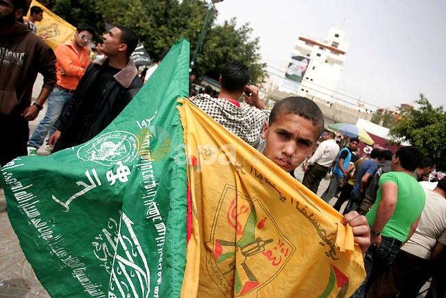 Palestinians wave with Hamas movement and Fatah party flags during a rally celebrating the signing of a reconciliation deal in Gaza city on May 4,2011.  Hundreds of Palestinians have gathered to cheer on a unity agreement being signed in Cairo between Hamas and Fatah. Photo by Mohammed Othman