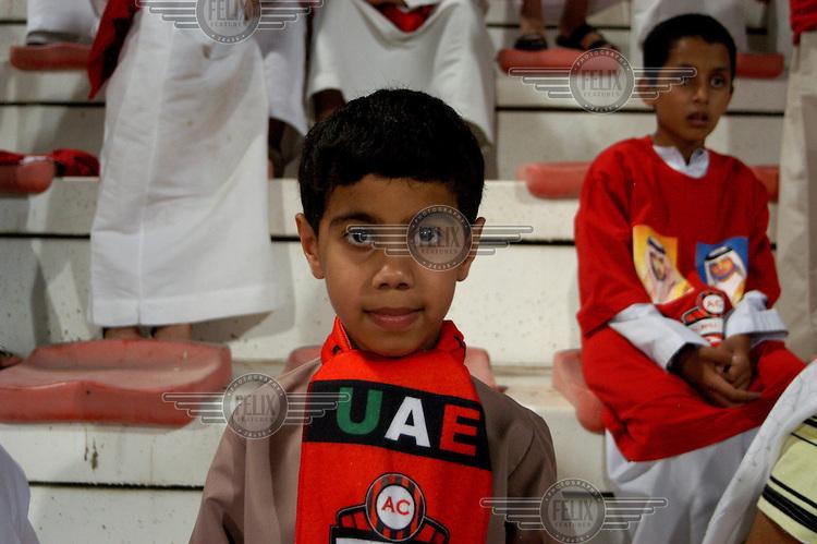 Boys watch a football match at a stadium in Deira. ..