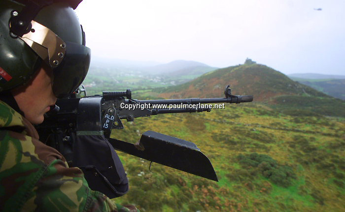 A British Army helicopter crewman looks out towards one of many security towers on Sturgeon Mountain, Camlough, South Armagh October  25, 2001.  Following the IRA starting to decommission its weapons, the British forces began to take down a number of security sites in Northern Ireland as a response.   REUTERS/Paul McErlane