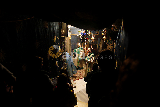 Christian worshippers pray inside the Grotto at the Church of the Nativity, believed to be the birthplace of Jesus Christ, in the West Bank city of Bethlehem, on December 18, 2016. Photo by Wisam Hashlamoun