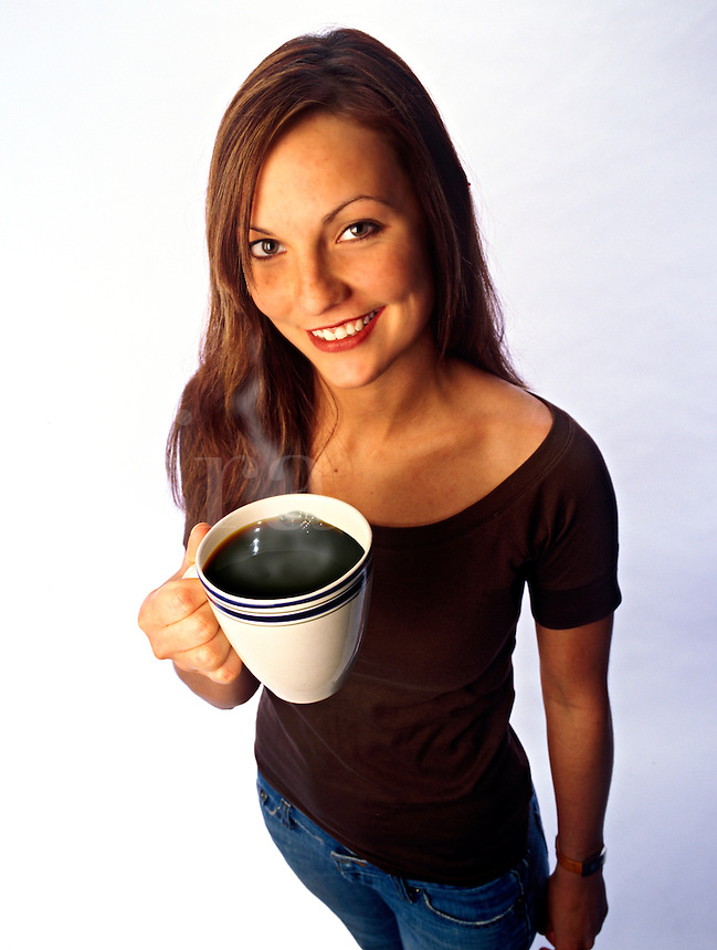 A young office worker with a steaming hot cup of coffee