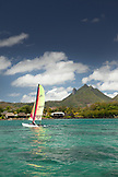 MAURITIUS, Trou D'eau Deuce, sailing in the Indian Ocean off the East coast of Mauritius with the 4 Sisters Mountains and the Four Seasons Resort in the background
