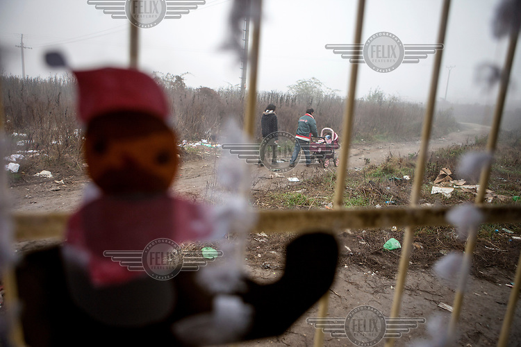 A couple push a child in a buggy past the barred windows of a children's play centre in the Roma settlement located in 'Budulovskej Street'.