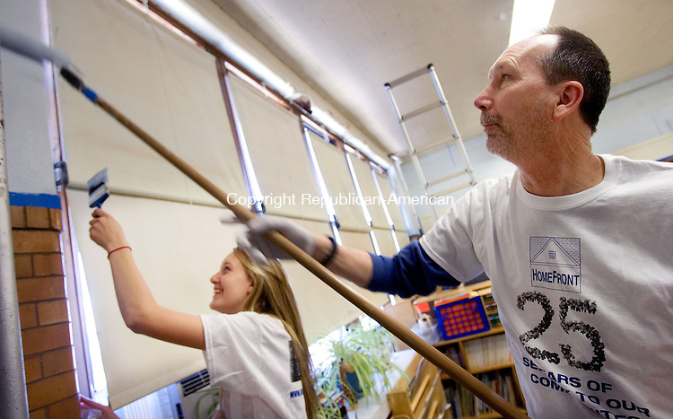WATERBURY CT. 04 May 2013-050413S02-From left, Emily Lind of Middlebury and her dad, Steve Lind of Middlebury, paint a classroom at Children's Community School in Waterbury Saturday. Volunteers were participating in the 25th annual HomeFront Day by painting at Children's Community School at 31 Wolcott Street in Waterbury..Steven Valenti Republican-American