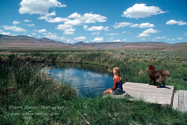 Woman and her dog enjoy a hot spring in Soldier Meadows
