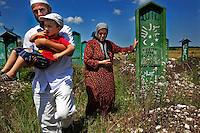 Fatima Davdieva visits a cemetery where many people who were killed in the war are buried. Fatima, her husband, and their three children fled Grozny ten years ago during the Second Chechen War as refugees. Now as Belgian nationals they return for the first time to visit their friends, family and former home.