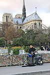 Man singing at Notre Dame Cathedral along the Seine River, Paris, France.