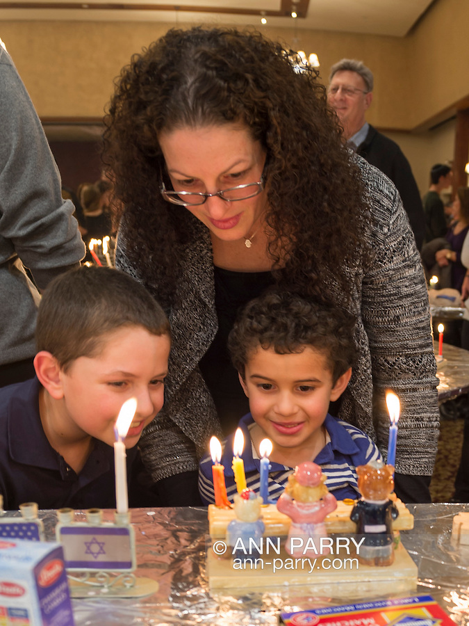 CARRIE BILITZKI, and her sons MATTHEW BILITZKI, 10, and JACOB BILITZKI, 5, look at Jacob's Three Bears menorah with four lit candles, at the Merrick Jewish Centre attempt to regain the Guinness World's Record for Most Menorot Lit in One Place at One Time that the congregation held in 2011. On the third night of Hanukkah, the 'Light Up the Night 2 - Bringing the Record Home' event also included a ceremonial candle lighting in the main sanctuary.