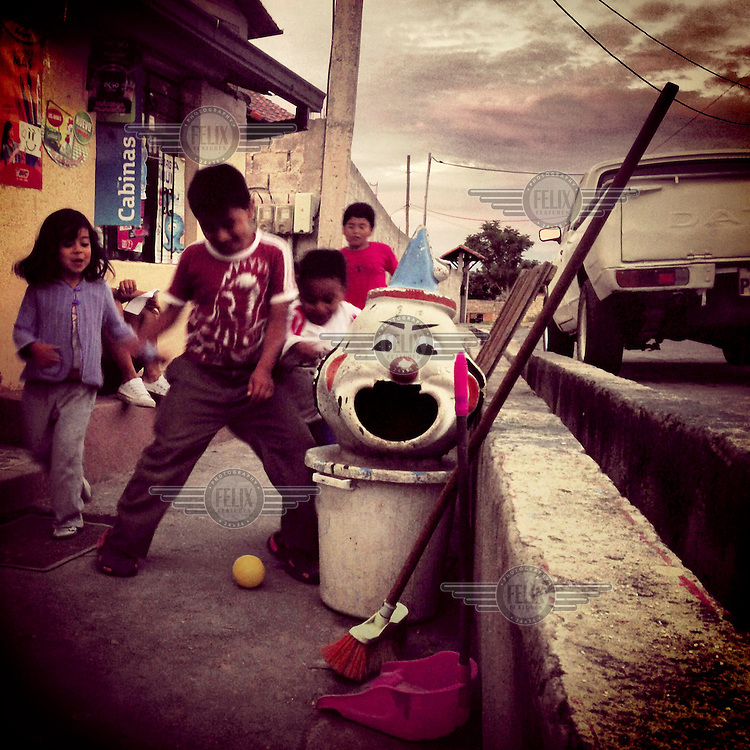 Children playing with a ball on a pavement beside a rubbish bin in the form of a clown.