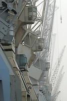 4415/Portalkrane: EUROPA, DEUTSCHLAND, HAMBURG 03.01.2006:Portalkrane aus alten Zeiten im Hamburger Hafen nahe Schuppen 50.  Ein Portalkran ueberspannt seinen Arbeitsbereich wie ein Portal. Das Portal ist eine Stahlkonstruktion ausgefuehrt in Fachwerks oder Rahmenbauweise. Der Kran hat jeweils eine Pendelstuetze und eine starre Stuetze um die temperaturbedingte Laengenaenderung der Kranbruecke (horizontaler Teil des Portals) auszugleichen. Auf der Kranbruecke verfaehrt die Laufkatze mit dem Hubwerk. Der Kran verfaehrt meist auf frei oder im Boden versenkten Schienen in horizontaler Richtung. Die Stromzufuehrung kann ueber eine Schleppleitung oder Schleifkontakte im Boden erfolgen. Portalkrane werden meist auf Gueterumschlagplaetzen und Lagerplaetzen eingesetzt..Museum der Arbeit...