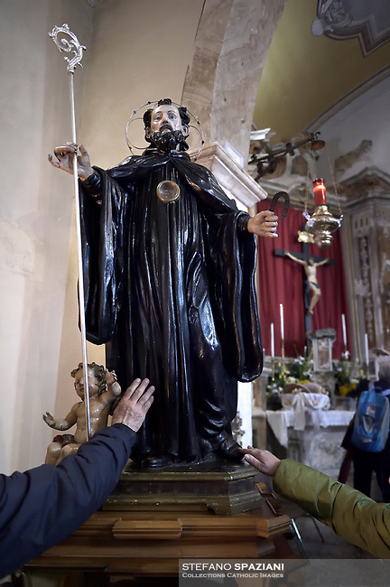 """The Statue of Saint Domenico inside the church of Cocullo before the procession.The feast of snakes. Process dedicated to the Saint Dominic, in the streets of Cocullo, in the Abruzzo region, Italy on May 1, 2019.<br /> <br /> <br /> <br /> The St. Domenico's procession in Cocullo, central Italy. Every year on the first  of May, snakes are placed onto the statue of St. Domenico and then the statue is carried in a procession through the town. St. Domenico is believed to be the patron saint for people who have been bitten by snakes:<br /> <br /> Italy, Cocullo, in the Province of L'A...quila, is at 870 meters a.s.l., along the railway line connecting Sulmona to Rome. The village rises alongside Mount Luparo (1327 meters) """"The valley opening in front of the village is surrounded by bare rocks, while on the other side, to the south, snow-capped mountain crests follow one after the other...""""<br /> San Domenico Abate lived in the 10th and 11th centuries AD. Born in Foligno, in the Umbria region, he started his pilgrimages, preaching and ascetic practices in Central Italy, making miracles recorded by the word-of-mouth tradition. He died on 22 January 1031 and was buried in Sora.<br /> <br /> Cocullo snake charmers are over with their snake hunting. They proceeded through the During the procession on the first in May, before the snakes are placed all over the statue of St. Dominick, they will be fed with milk kept in containers with crusca. It is the snake that, most of all other elements, expresses an ancestral myth: the unknown aspect and unpredictability of the natural environment with man's innate need to achieve the dominance on his own habitat. <br /> <br /> Snakes and wolves were the emblems of Italic peoples like the Marsians and Irpinians. Some areas in Abruzzo, especially in the Sagittario valley, were under the menace of wolves and snakes, which for the local populations represented the uncertainty and anxiety of their existence that, together with the precariousn"""
