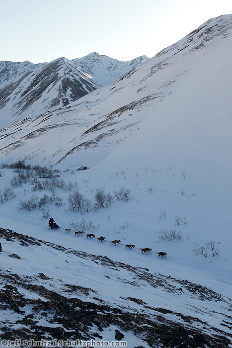 Sebastian Schnuelle on the trail nearing the summitt of Rainy Pass with the Alaska Range in the background during Iditarod 2011