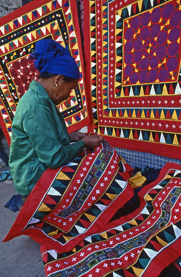 Lao woman stitches bright traditional Lao fabric on Vientiane sidewalk