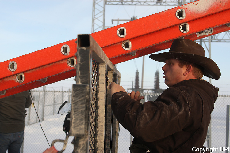 Ammon Bundy unties a ladder used to remove two FBI surveillance cameras found at a power station near the Malheur National Wildlife Reserve on January 15, 2016 in Burns, Oregon.  Bundy and about 20 other protesters took over the refuge on Jan. 2 after a rally to support the imprisoned local ranchers Dwight Hammond Jr., and his son, Steven Hammond. Another surveillance camera was found near the reserve.    Photo by Jim Bryant/UPI