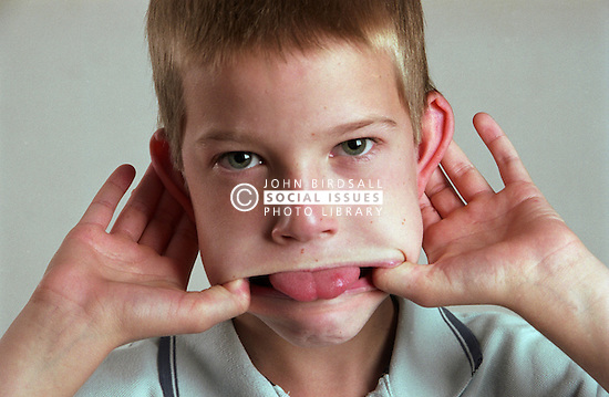 Portrait of young boy pulling face and sticking tongue out,