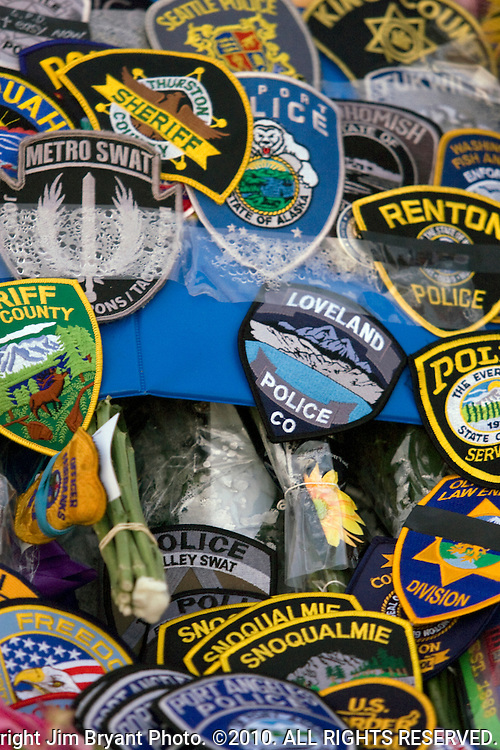 Police department patches, flowers, balloons, stuff animals, pictures and  wreaths were left to form a makeshift memorial to four slain police officers at the Police Headquarters in Lakewood, Washington, USA, on 2 December  2009. Four Lakewood officers were gunned down during a morning meeting at a local coffee shop on 29 November 2009. Jim Bryant Photo. ©2010. ALL RIGHTS RESERVED.