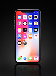 Apple iPhone X, large screen smartphone, product still life with desktop and app icons on its colorful red blue display standing upright isolated on black background with a clipping path.