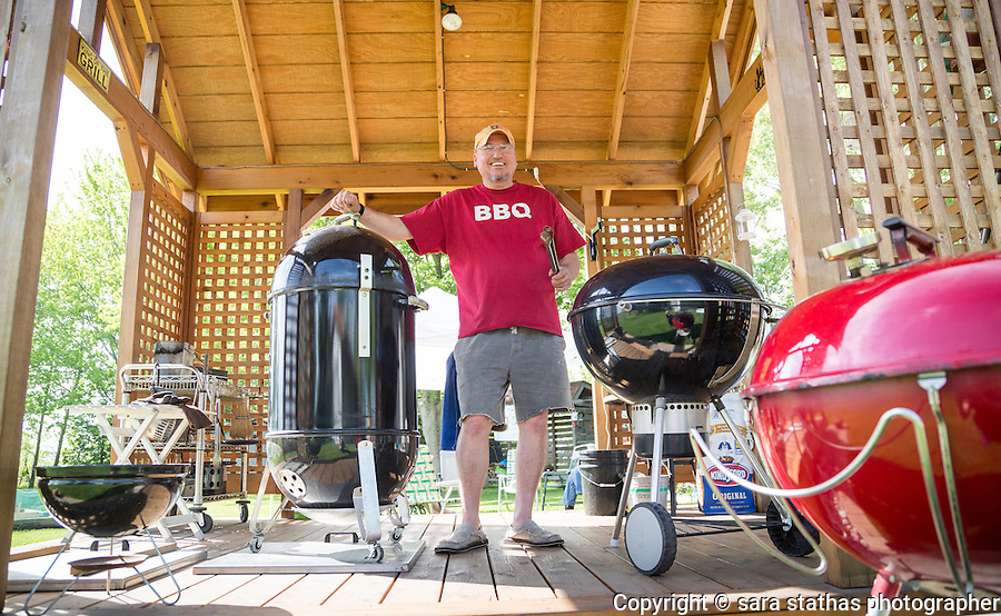"Jim Lampe, 54, of Raymond, Wisconsin, prepares to smoke seven racks of pork spare ribs in his backyard ""pigvilion"" for a Memorial Day Weekend gathering of friends and family. CREDIT: Sara Stathas for The Wall Street Journal. SMOKIN"