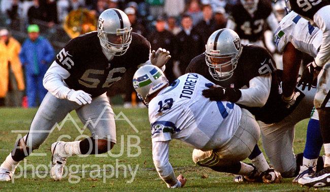 Oakland Raiders vs. Seattle Seahawks at Oakland Alameda County Coliseum Sunday, December 22, 1996.  Seahawks beat Raiders  28-21.  Oakland Raiders linebacker Pat Swilling (56) and defensive tackle Chester McGlockton (91) sack Seattle Seahawks quarterback Gino Torretta (13).