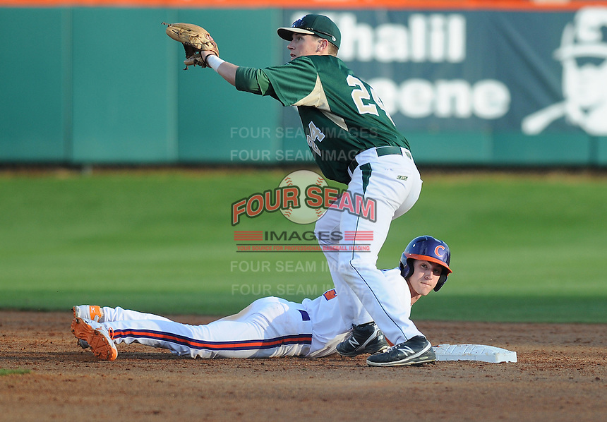 Byrnes product right fielder Steven Duggar (9) of the Clemson Tigers slides safely back into second in a pickoff attempt with Ryan Williams (24) of the William & Mary Tribe trying to make the putout on Opening Day, Friday, February 15, 2013, at Doug Kingsmore Stadium in Clemson, South Carolina. Clemson won, 2-0. (Tom Priddy/Four Seam Images)