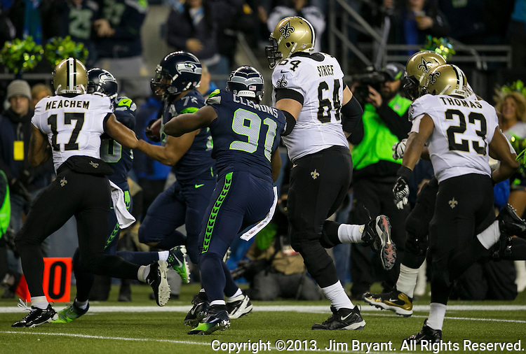 Seattle Seahawks  defensive end Michael Bennett returns a fumble for a 22-yard ouchdown against the New Orleans Saints during the first quarter at CenturyLink Field in Seattle, Washington on December 2, 2013. The Seahawks beat the Saints 34-7 to take the best record team in the NFL.©2013. Jim Bryant Photo. ALL RIGHTS RESERVED.