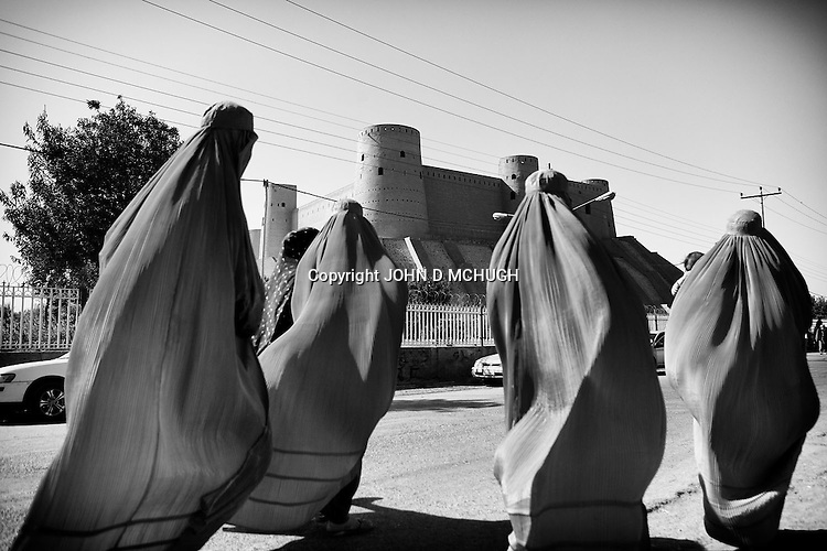 Women wearing traditional burghas walk past the ancient Citadel fortress in Herat, 22 September 2013. (John D McHugh)