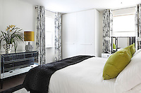 Curtains illustrated with lively pen and ink street scenes adds variety to the simple, monochrome colour scheme of this bedroom