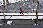 A photo of a man running across a tressle bridge on a snowy day near Truckee in California