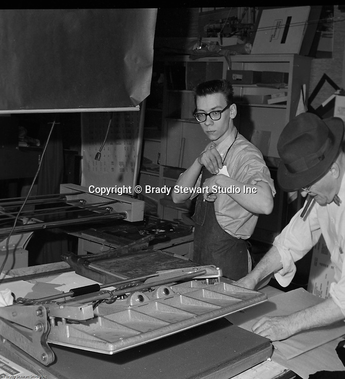 Pittsburgh PA:  Robert Pavuchak getting ready to trim prints to complete a job while Brady Stewart Sr is preparing a print for mounting on cardboard - 1959.  Our copy camera is in the background and a mounting press in the foreground.  We continued to use the same equipment until 1991.