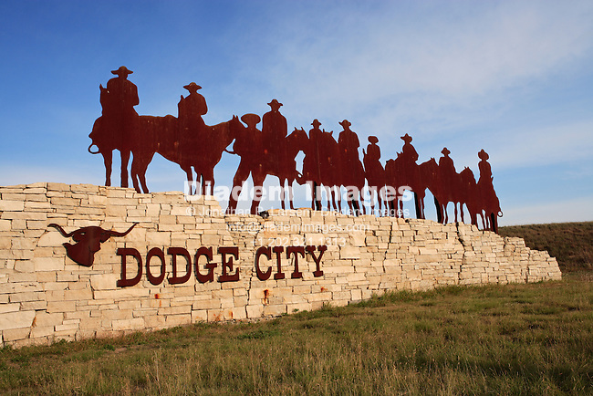 A city sign and sculpture of silhouetted cowboys and horses at the entrance to Dodge City, Kansas, USA.