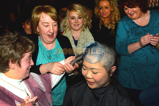 Erin O'Connor has her head shaved to raise funds for the Gary Kelly Cancer Support Centre and the Bone Marrow for Leukaemia Trust. Doing the honours is hairdresser Clare Murphy. Photo: Andy Spearman. www.newsfile.ie www.newsfile.ie