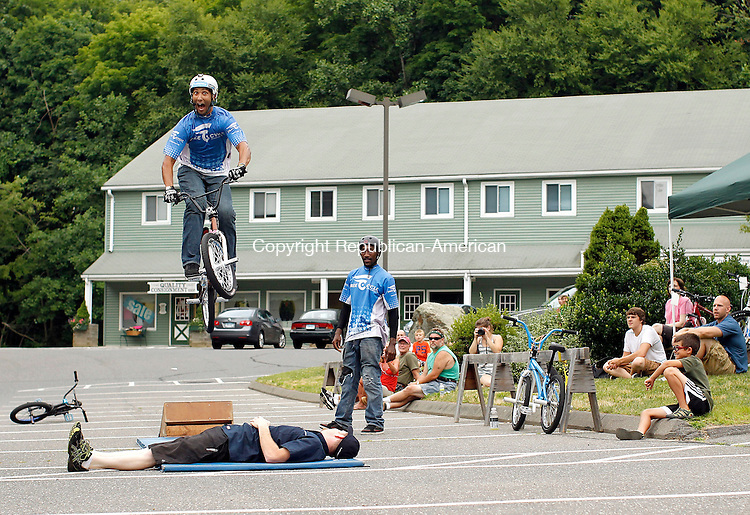 Middlebury, CT-07 July 2012-070712CM01- Jason Rodriguez an athlete with The FreeCycle Action Sports Team jumps over Matt Morris, owner of Bicycle Works of Middlebury during a bike stunt show Saturday afternoon.  The annual Stunt Show and Demo day featured athletes showing off their cycling skills.  The event also featured a raffle of a custom bike, with all of the proceeds benefiting Are You Dense Inc. of Woodbury, a nonprofit breast cancer support organization.     Christopher Massa Republican-American