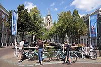 Nederland Delft - Augustus 2018.  Toeristen op de fiets in Delft. Op de achtergrond de Oude Kerk.    Foto Berlinda van Dam / Hollandse Hoogte