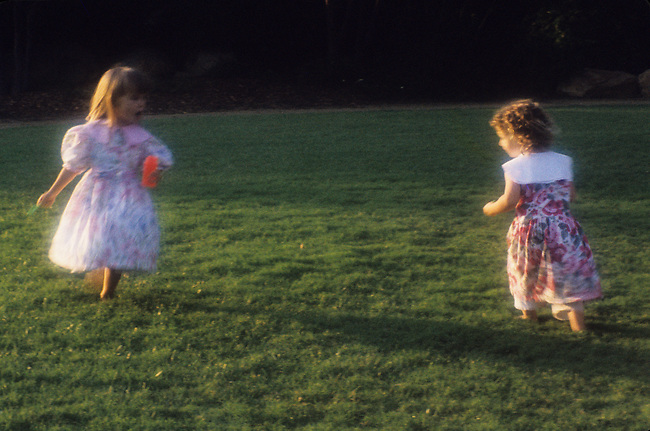 Young girls playing together blowing soap bubbles.MODEL RELEASED