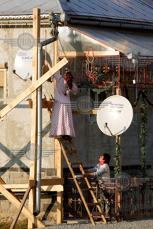 A Roma gypsy woman balances on a ladder above two large satellite TV dishes in order to hang Christmas lights along the roof of her home.