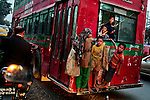 Bangladeshi street children hang onto a moving bus in Dhaka, Bangladesh.
