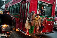 Bangladeshi street children hang onto a moving bus in Dhaka, Bangladesh.