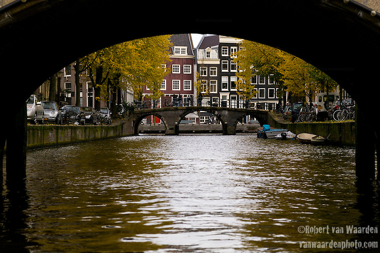Canal in Amsterdam, the Netherlands, framed by a canal bridge and backdropped by yellow autumn colors.