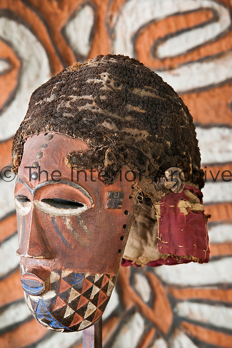 A Kubakete Congo mask displayed in front of a colorful pattern